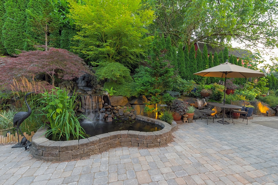 Beautiful backyard, natural stone paved patio with complementary landscaping