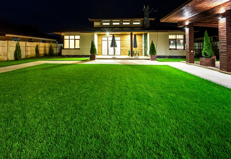 Nighttime shot of courtyard and front and side of house with beautifully manicured lawn